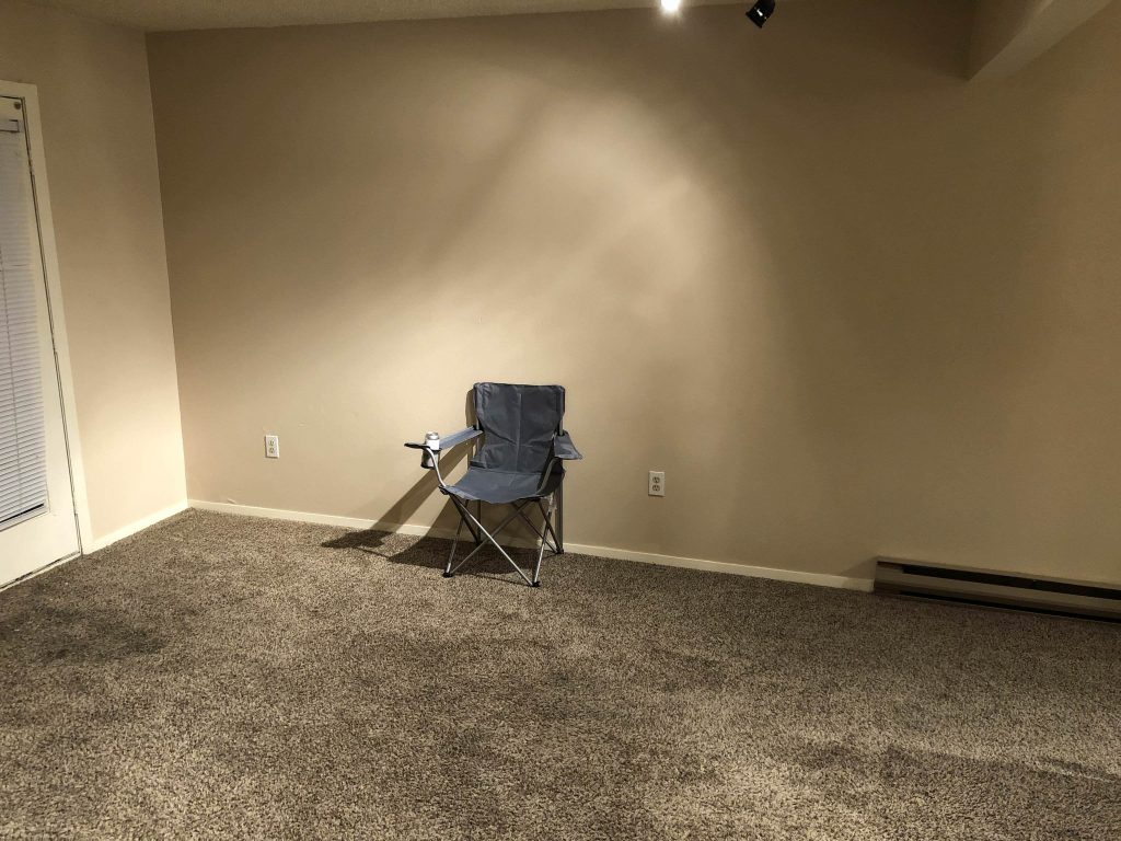 Just a camp chair in a bare living room