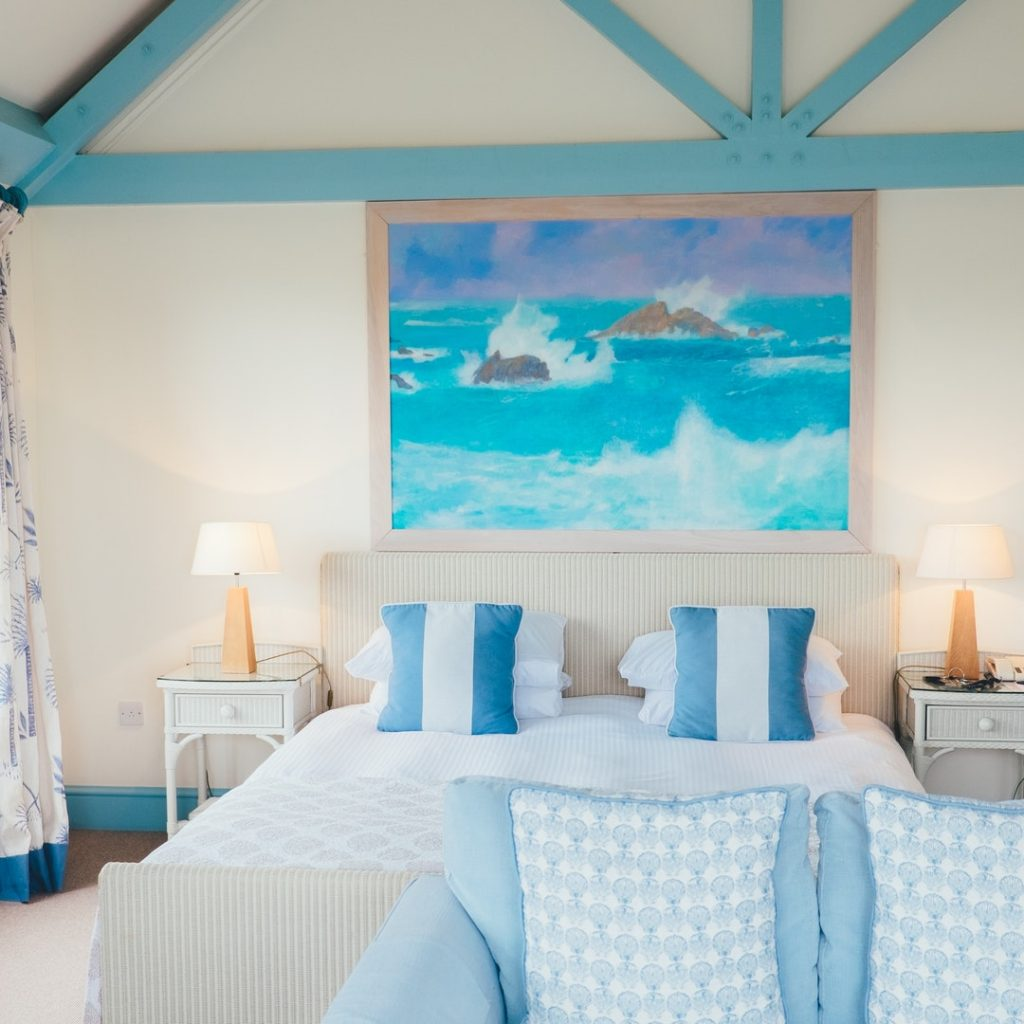 a coastal style bedroom setting with double bed nicely made up and a blue and white color scheme in the room