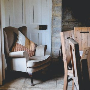 farmhouse setting with grey wing back armchair in front of a white door and next to rustic wooden dining chairs to the right