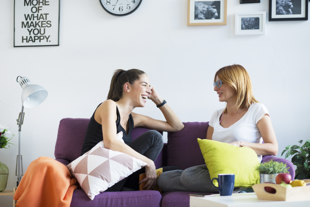 Two women chatting and having fun on the sofa