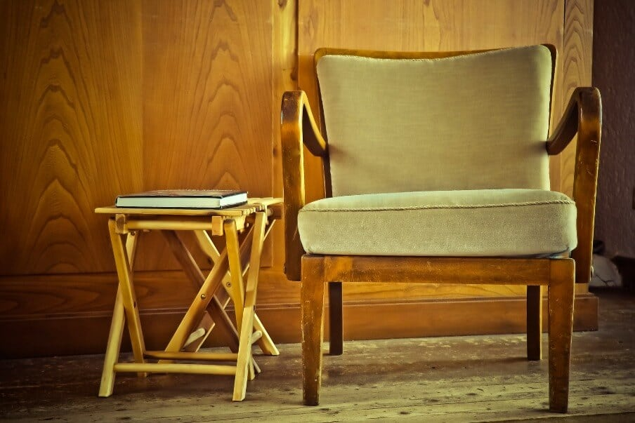 wood framed accent chair next to a wooden fold away combination stool and side table