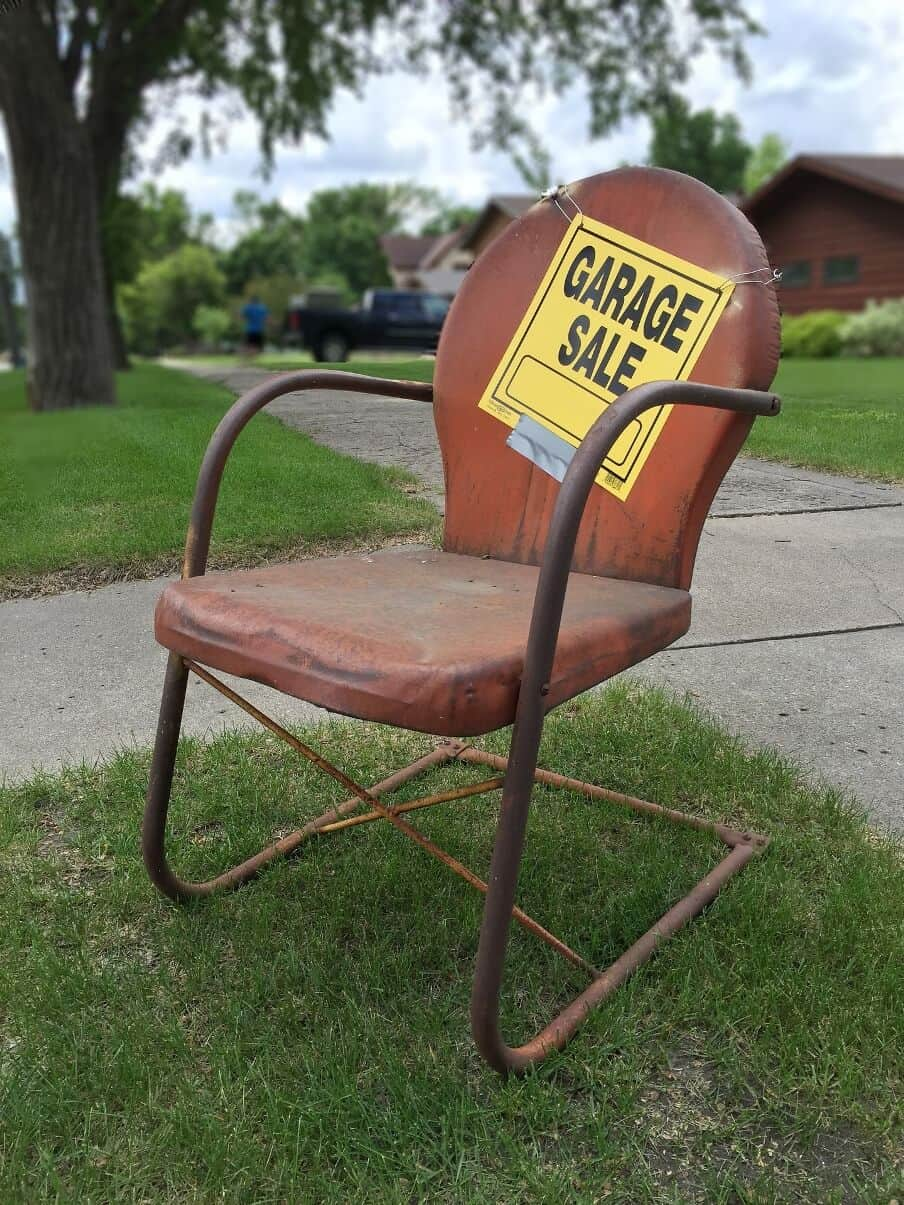 old metal framed chair with cushion with a garage sale sign hung on it