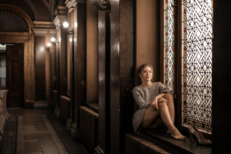 a dark hall with a young lady perched in a window recess