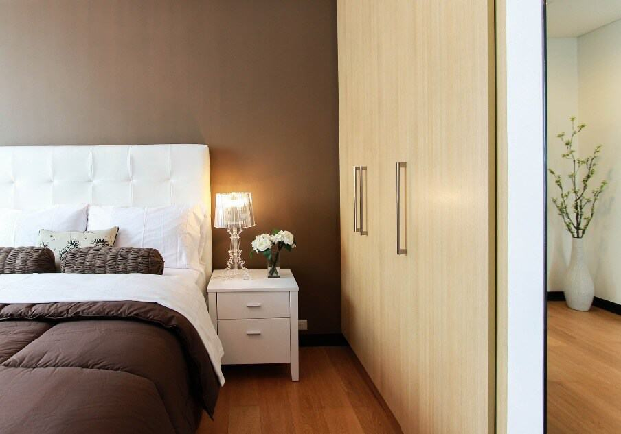 bedroom setting with bed with brown quilt and wall color behind is brown