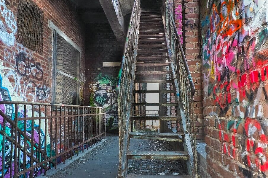 a set of metal stairs and railings within a brick lined landing space
