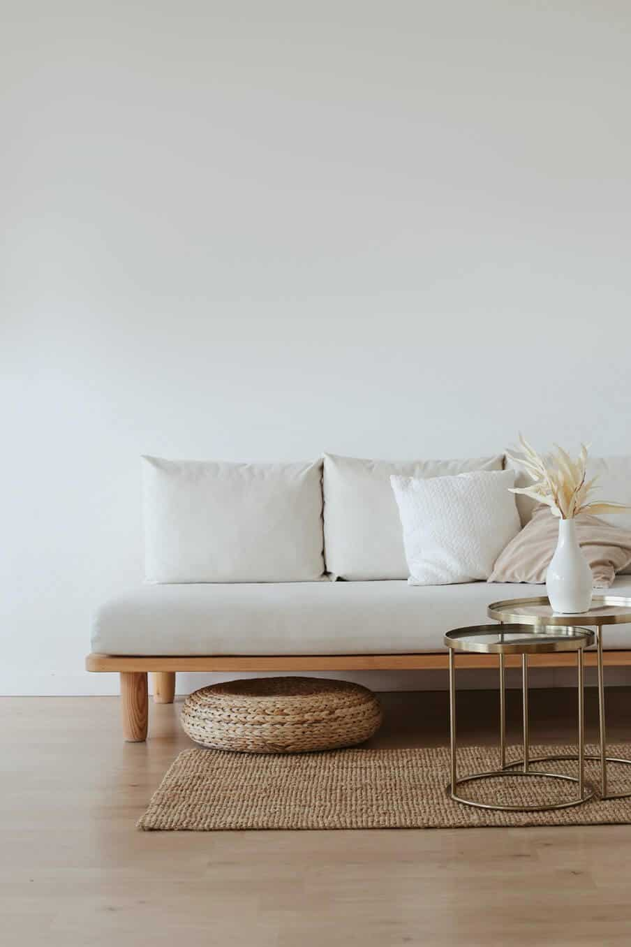 A simple timber framed sofa and cushions sitting on a wooden floor